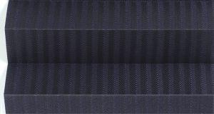 Plissegardin LUX betjenes med håndtak. Mønstret tekstil